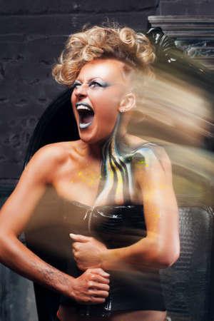 rocker girl: Retrato de mujer gritando el punk larga exposición. chica del eje de balancín con el arte del cuerpo brillante, maquillaje y peinado, escapar de su dolor. La angustia, el arte del cuerpo, la agresión, el estilo de vida, el concepto de la psicoterapia