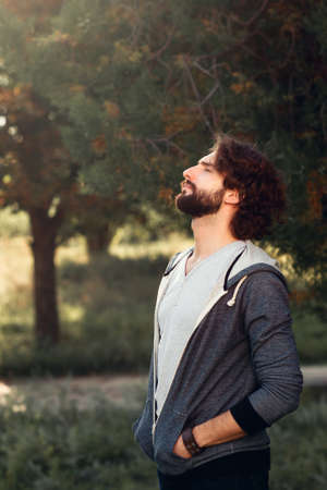 free space: Young man having sunbath in forest, side view. Profile of attractive guy enjoying sunlight, free space for text. Rest, relax, calm, last summer warm concept