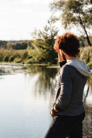 pacification: Young stylish guy enjoying calm nature landscape. Man looking at river water, back view, free space. Pacification, relax, thoughts concept