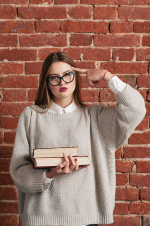 cansancio: Tired student with books shows shooting gesture. Exhausted girl need rest from intensive tutorial. Education, tiredness concept Foto de archivo