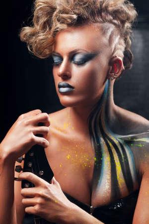 rocker girl: Punk mujer posando con los ojos cerrados retrato. rocker girl hermosa con maquillaje agresivo, el arte del cuerpo y peinado sienta con la guitarra. Subcultura, estilo de vida, afición, expresión, concepto de moda Foto de archivo