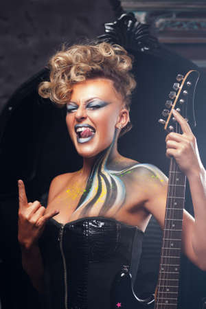 rocker girl: Impressed woman punk showing metal horns. Rocker girl in courage posing at camera with her bass guitar, bright makeup and hairstyle. Subculture, lifestyle, art, music, drive concept Foto de archivo