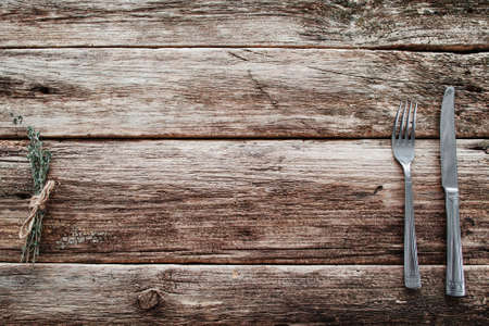 grunge cutlery: Rustic wooden table with knife and fork free space. Top view on grunge rural background with cutlery and herbs, background for meal advertisement or restaurant menu Stock Photo