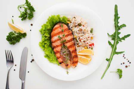 サーモンのグリル、ライスとカトラリーがフラットが横たわっていた。野菜のリゾットと赤魚ステーキのレストランの平面図です。地中海料理、シ