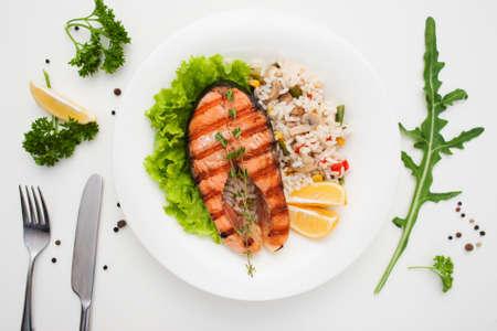 구운 연어와 쌀과 칼 붙이 평면 누워. 야채 리조또와 빨간 물고기 스테이크의 레스토랑 봉사에 상위 뷰. 지중해 요리, 해산물 메뉴, 건강 식품 컨셉