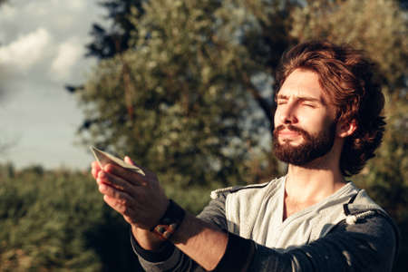pacification: Man praying with paper plane in hands free space. Young guy standing with closed eyes and peaceful expression on face, holding paper airplane. Calm, pacification, relax concept