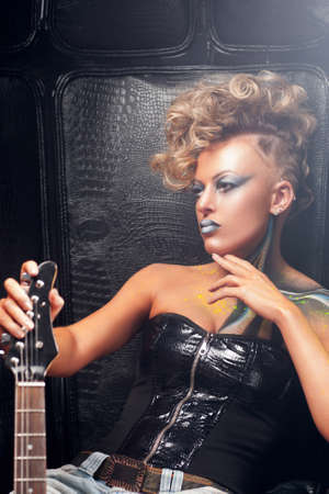 rocker girl: Pensive rocker girl posing with guitar free space. Serious punk woman with bright body art and hairstyle with musical instrument. Subculture, lifestyle, hobby, expression, fashion concept Foto de archivo