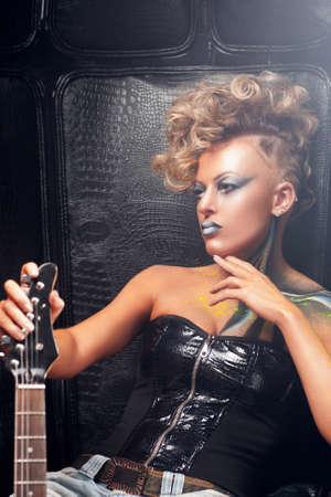 rocker girl: rocker girl pensativo que presenta con el espacio libre de la guitarra. Mujer punky serio con el arte del cuerpo brillante y peinado con el instrumento musical. Subcultura, estilo de vida, afición, expresión, concepto de moda