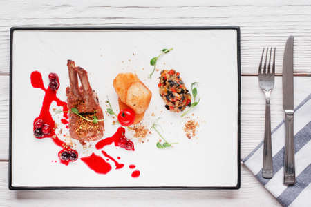 expensive food: Restaurant serving of grilled ribs flat lay. Top view on white tray with meat, potato and vegetable mix with cherry sauce and cutlery. Expensive food, luxury lifestyle, recipe concept