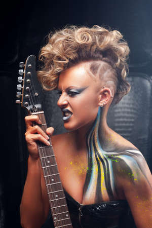 rocker girl: Impressed punk musician playing on guitar. Portrait of rocker girl with bright body art, emotionally performing. Subculture, expression, courage, drive, rock, lifestyle concept