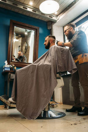 hairtician: Man cut hair at barber shop free space. Side view on modern confident businessman at beauty salon. Fashion, style, glamour, business concept Stock Photo