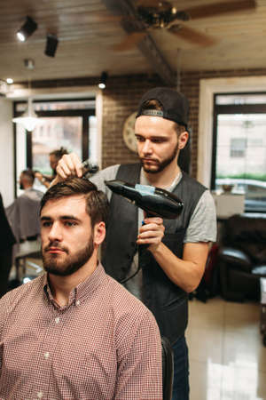 hairtician: Stylist making modern hairdo for young man. Successful businessman sitting at barber shop and dry hair. Style, beauty, modern life concept