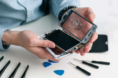 Repairman disassembling smartphone close-up. Male hands holding opened mobile phone for diagnostics, repair tools on workplace. Electronic fixing, modern technology, business concept