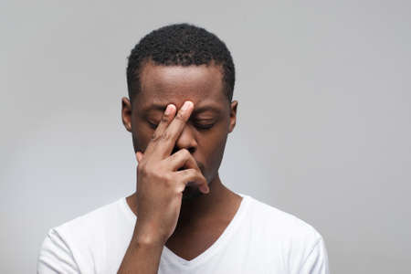 Thoughtful young african american man with closed eyes on grey background with free space for text.
