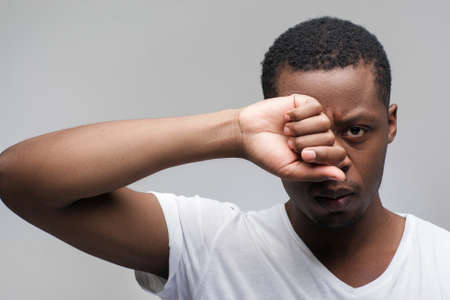 Tired young african american man wearing white t-shirt. Feeling of anger, rage, offence, resentment. Portrait on grey background with free space for text.