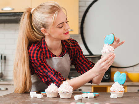 craftmanship: Girl decorating cup cakes with white cream and blue cake-pops at kitchen wooden table. Culinary masterclass. Easter gift, small business, delivery of sweets, craftmanship concept