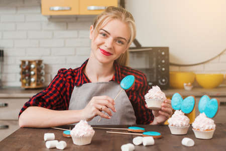 craftmanship: Young smiling woman cooking homemade cup cakes in kitchen. Culinary masterpiece. Easter gift, small business, delivery of sweets, craftmanship concept Stock Photo