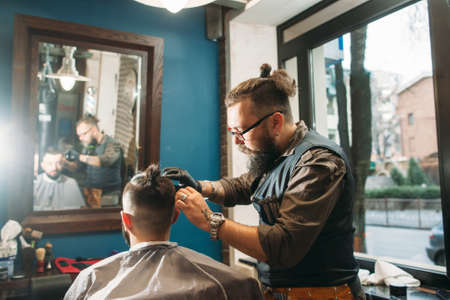 hairtician: Senior barber finishing stylish hairdo free space. Bearded hairtician cut man, workplace interior background. Beauty, style, modern life, barbershop concept