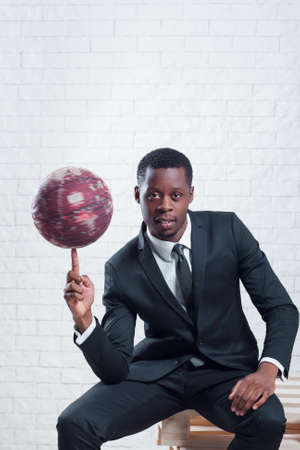 Successful african sportsman with a basketball wearing business suit on white brick wall background. Reklamní fotografie