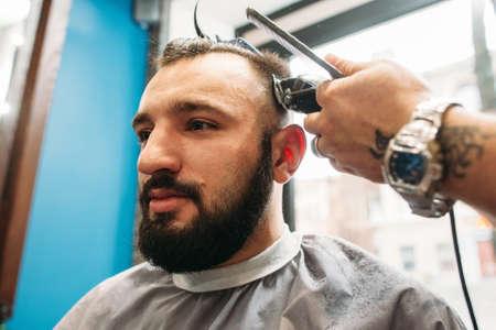 hairtician: Young man sitting at stylist closeup. Modern brunet making hairstyle at barber shop. Beauty, modern lifestyle, fashion, glamour, style, business concept Stock Photo