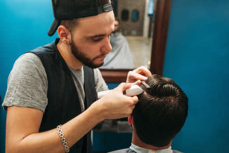hairtician: Young barber cut man hair free space. Professional hairtician making hairdo for brunet, sitting at mirror. Beauty, barbershop, occupation, style, modern life concept