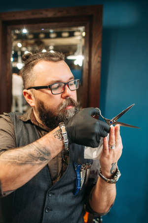 haircutting: Professional hairdresser teach how to cut hair. Bearded experienced barber holding scissors and check their sharpness, free space. Barbershop, beauty, master class concept Stock Photo