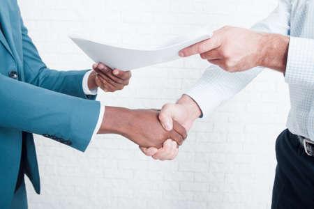 Handdruk op kantoor na het sluiten van een deal. Twee ondernemers van het bedrijf hebben een contract getekend voor interraciale samenwerking. Stockfoto