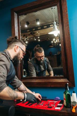hairtician: Barber preparing instruments for work free space. Senior bearded hairtician check work tools for haircut at his workplace against mirror. Barbershop concept