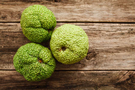 hedgeapple: Several Adams apples on wood flat lay. Top view on old grungy wooden background with three green osage oranges, free space for text. Exotic, gourmet concept Stock Photo