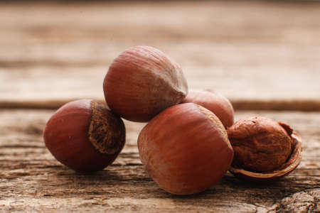 nutshells: Filbert nuts on wood close-up. Several hazelnuts with one peeled. Brown autumn background. Harvest, fall, food ingredient concept