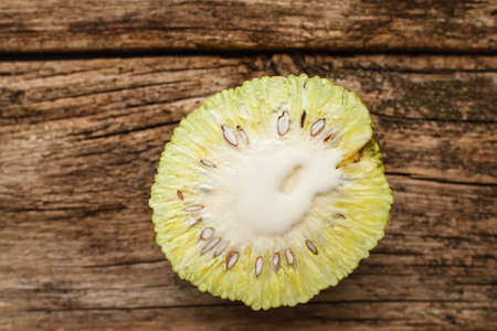 hedgeapple: Half of fresh osage orange on wood flat lay. Top view on cut exotic Adams apples fruit on old wooden background, free space for text. Tropical, alternative medicine, pharmacology concept Stock Photo