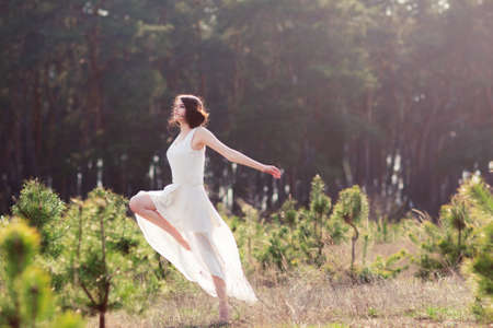 Contemporary dances in nature. Woman in flying white dress dancing in forest