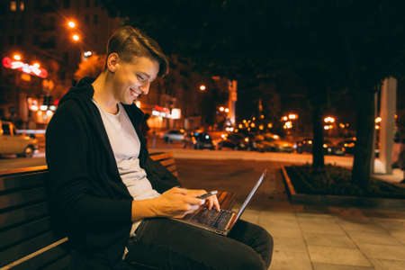 he: Young guy chatting in city street in night time, blurred lights background, free space. Smiling guy reading message on smartphone, while he working on laptop outside.