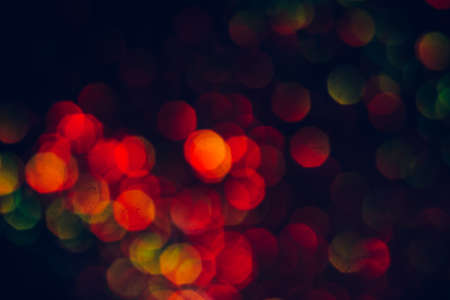 Abstract blurred glittering shine, green and red. Blur light bokeh, night background. Christmas wallpaper decorations concept. New year holiday festive backdrop. Sparkle circle celebrations display. Stock Photo
