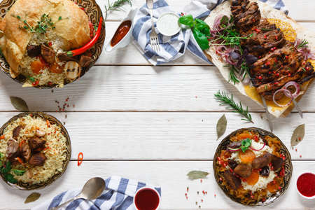 advertizing: Variety of georgian cuisine dishes with meat on wood table. Shah pilaff, kebab and different types of rice with meat on free space background Stock Photo