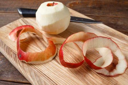 Einzelner roter Apfel, der durch Messer schneidet. Schließen Sie herauf die frische Frucht, die auf hölzernen Schreibtisch gelegt wird. Gesundes Essen, diätetisch, Konzept zu kochen