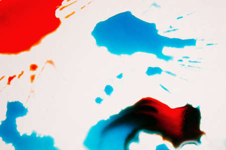 Abstract image of colorful splashes on white background. Watercolor plumps of bright red and turquoise paints with black blots on surface Stock fotó