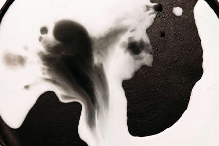 ink stain: Abstract image of white liquid streaks on black background. Watercolor blots of milk spread on surface and flowing each other