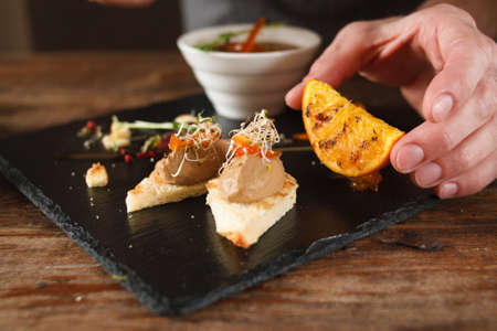 Culinary art of serving appetizers in restaurant. Unrecognizable man lays grilled orange and herbs near small canapes with paste on black tray