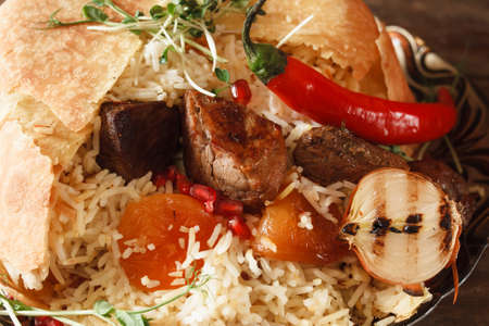 advertizing: Close up of shah pilaff on big plate. National georgian cuisine, spicy rice with meat under lavash decorated chili pepper, dried apricots and grilled onion Stock Photo