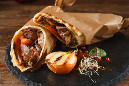 advertizing: Shawarma rolled in baking paper and layed on black plate. Lavash, moist meat with grilled onion, herbs and spices on wooden background