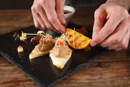 레스토랑에서 전채 요리의 요리 예술. 붙여 넣기가 가능한 작은 카나페, 검은 색 트레이에 구운 오렌지와 허브 장식