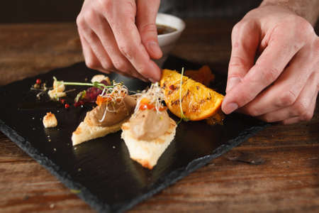 Culinary art of serving appetizers in restaurant. Small canapes with paste, decorated grilled orange and herbs on black tray Stock Photo