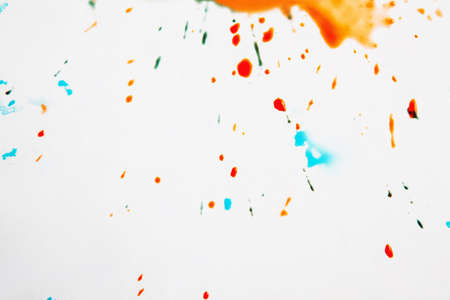 Abstract image of colorful drops on white background. Watercolor drops of red, green, orange and turquoise colors on surface. Free space