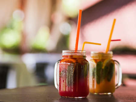 Fresh fruit cocktails in glass jars on wooden table. Orange and strawberry cold drinks with mint and ice, refreshment in hot weather, close up picture with free space