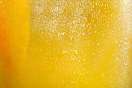 Background of fresh cold citrus cocktail. Close up picture of glass wall of orange drink with drops of water, refreshment and coolness concept