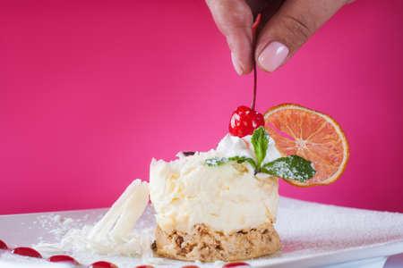 Decoratie van romig oranje dessert door kers. Heerlijke cake met gedroogde citrus, witte chocolade en munt op karmozijnrode achtergrond, echt plezier van snoep. Afbeelding sluiten Stockfoto