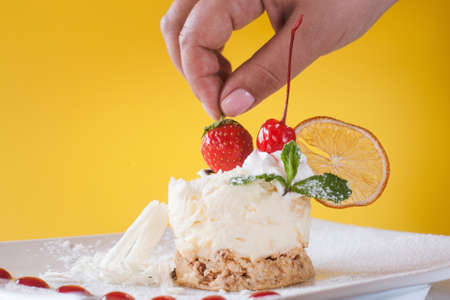 Decoratie van romig oranje dessert door kers. Heerlijke cake met gedroogde citrus, witte chocolade en munt op gele achtergrond, echt plezier van snoep. Afbeelding sluiten Stockfoto