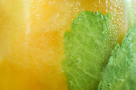 Background of fresh cold citrus cocktail with mint. Close up picture of glass wall of orange drink with drops of water, refreshment and coolness concept