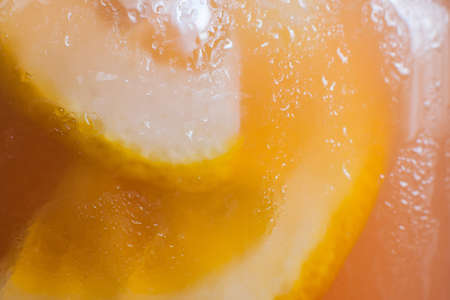 Background of fresh cold citrus lemonade. Close up picture of glass wall of fruit drink with drops of water and sliced orange shape, refreshment and coolness concept